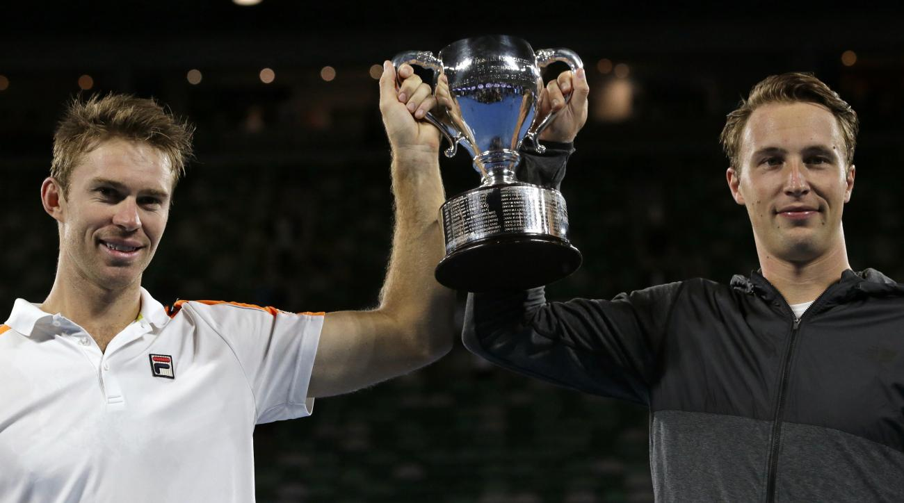 Finland's Henri Kontinen, right, and Australia's John Peers hold their trophy aloft after winning the men's doubles final against Bob and Mike Bryan of the U.S. at the Australian Open tennis championships in Melbourne, Australia, Saturday, Jan. 28, 2017.