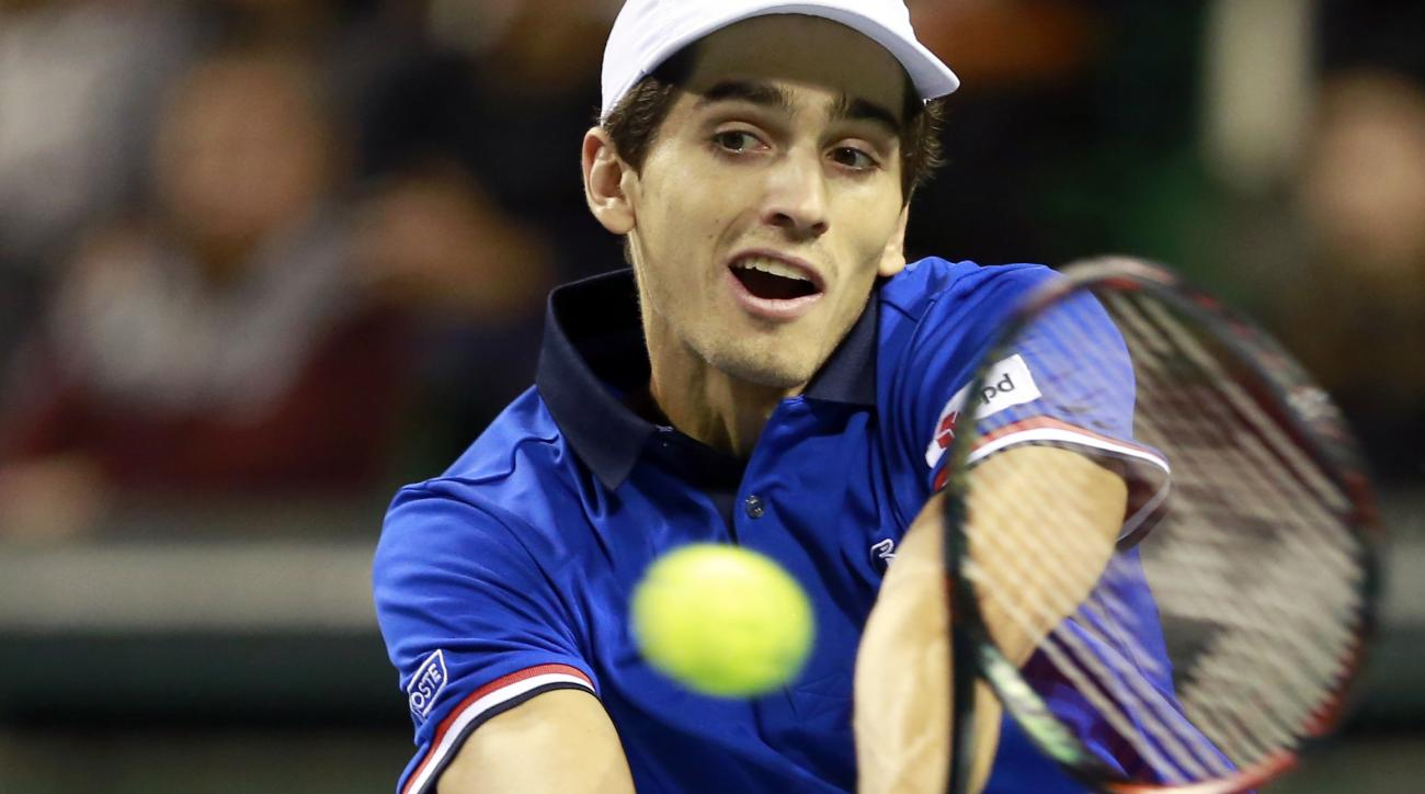 France's Pierre-Hugues Herbert returns the ball against Yasutaka Uchiyama of Japan during their Davis Cup World Group first round tennis match in Tokyo, Sunday, Feb. 5, 2017. France qualified already on Saturday for the next round, after winning the first