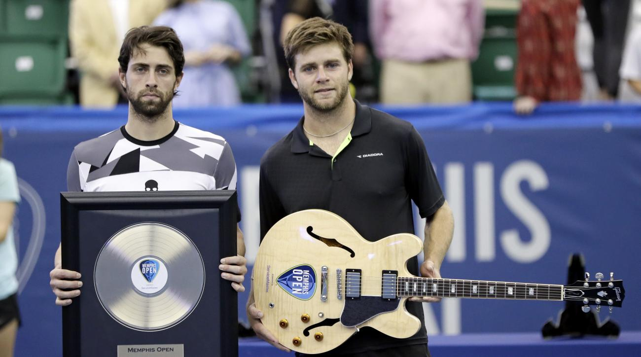 Ryan Harrison, of the United States, right, and Nikoloz Basilashvili, of Georgia, left, pose with their trophies after Harrison defeated Basilashvili in the singles championship at the Memphis Open tennis tournament Sunday, Feb. 19, 2017, in Memphis, Tenn
