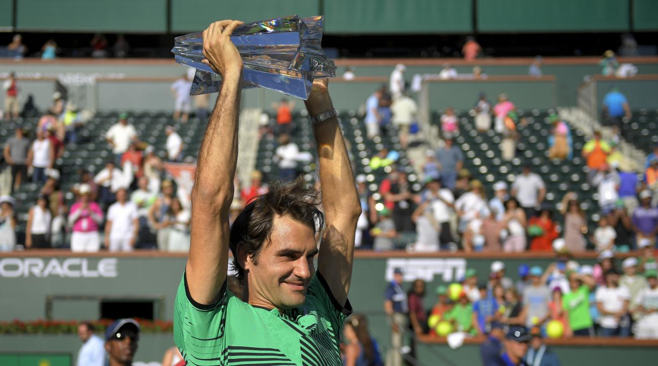 Roger Federer, of Switzerland, celebrates with the trophy after his win against Stanislas Wawrinka, of Switzerland, in the finals of the BNP Paribas Open tennis tournament, Sunday, March 19, 2017, in Indian Wells, Calif. (AP Photo/Mark J. Terrill)