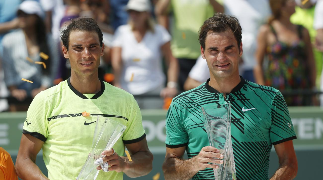 Rafael Nadal, of Spain, left, and Roger Federer, of Switzerland, hold their trophies as they pose for photos after the men's singles final tennis match at the Miami Open, Sunday, April 2, 2017, in Key Biscayne, Fla. Federer defeated Nadal. (AP Photo/Wilfr