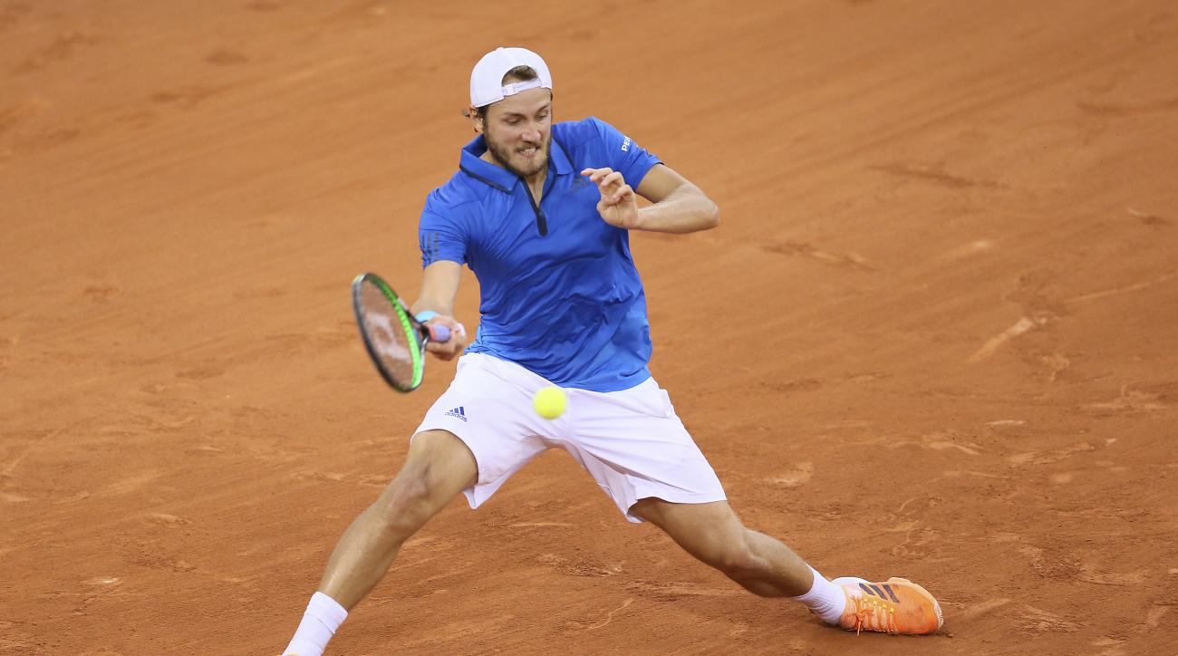 Lucas Pouille of France returns the ball to Kyle Edmund of Great Britain during their Davis Cup quarterfinal tennis match between France and Great Britain at the Kindarena Stadium of Rouen, France, Friday, April 7, 2017. (AP Photo/David Vincent)
