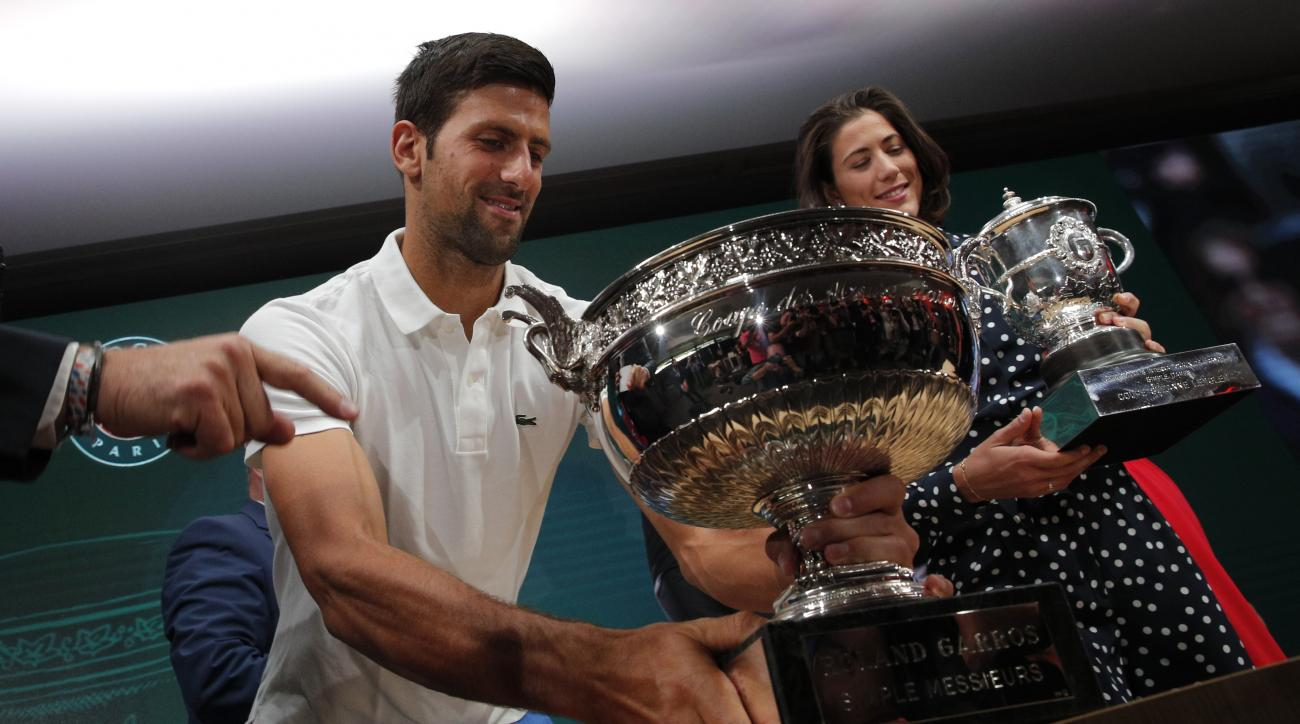 Defending champions Serbia's Novak Djokovic and Spain's Garbine Muguruza carry the cups as they arrive for the draw of the French Open tennis tournament at the Roland Garros stadium, Friday, May 26, 2017 in Paris. The French Open tennis tounament starts S