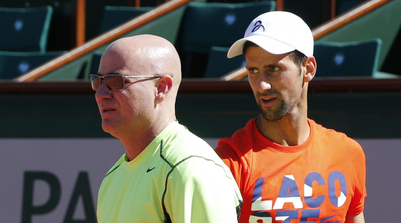 Defending champion Serbia's Novak Djokovic watches Andre Agassi, left, of the U.S, during a training session for the French Open tennis tournament at the Roland Garros stadium, Friday, May 26, 2017 in Paris. Agassi is Djokovic's new coach. (AP Photo/Chris