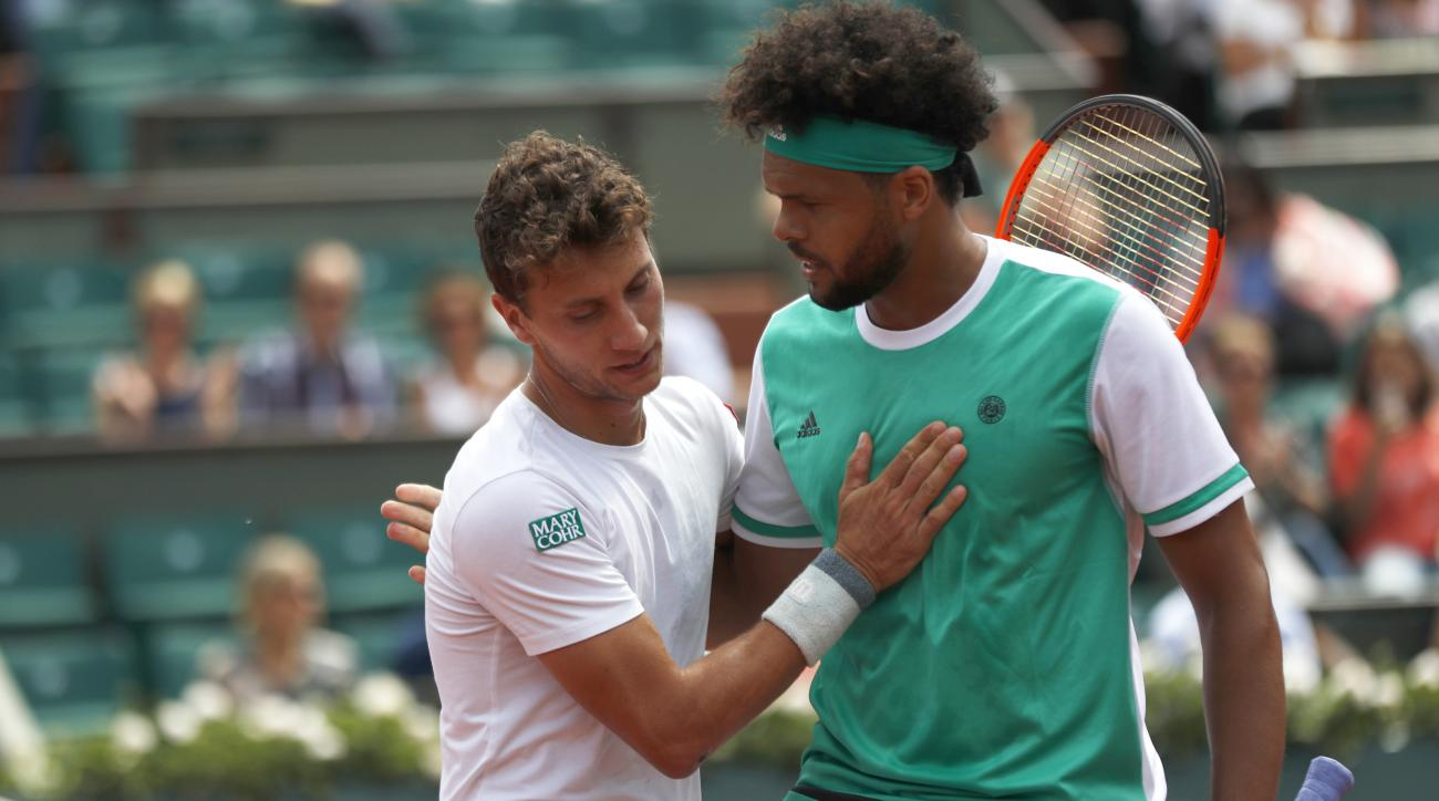 Argentina's Renzo Olivo is congratulated by France's Jo-Wilfried Tsonga after winning his first round match of the French Open tennis tournament at the Roland Garros stadium, in Paris, France. Wednesday, May 31, 2017. (AP Photo/Petr David Josek)
