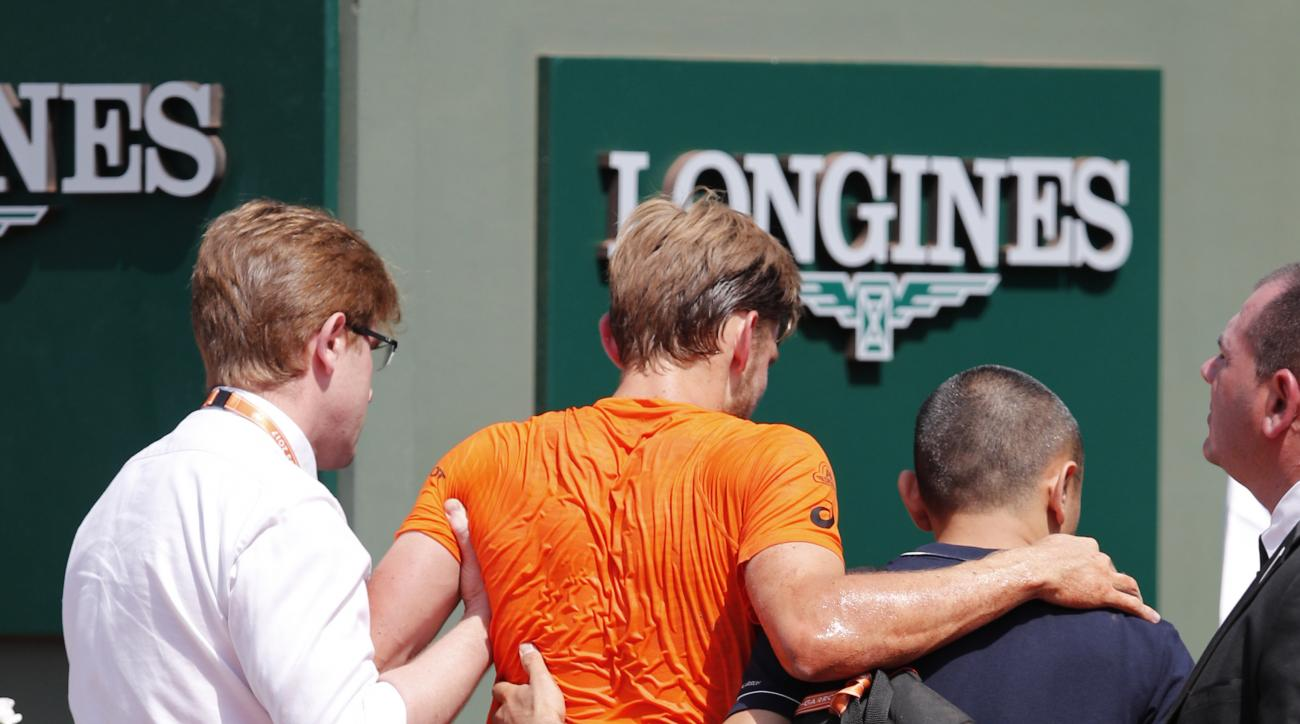 Belgium's David Goffin is taken to medical care after falling in his match against Argentina's Horacio Zeballos during their third round match of the French Open tennis tournament at the Roland Garros stadium, in Paris, France. Friday, June 2, 2017. (AP P