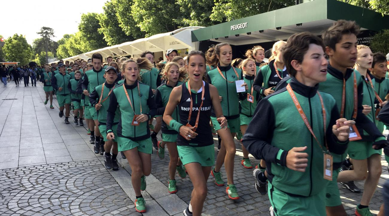 Ball boys and girls jog in the alleys of the Roland Garros stadium before the start of matches of the French Open tennis tournament, Wednesday, June 7, 2017 in Paris. (AP Photo/Bertrand Combaldieu)