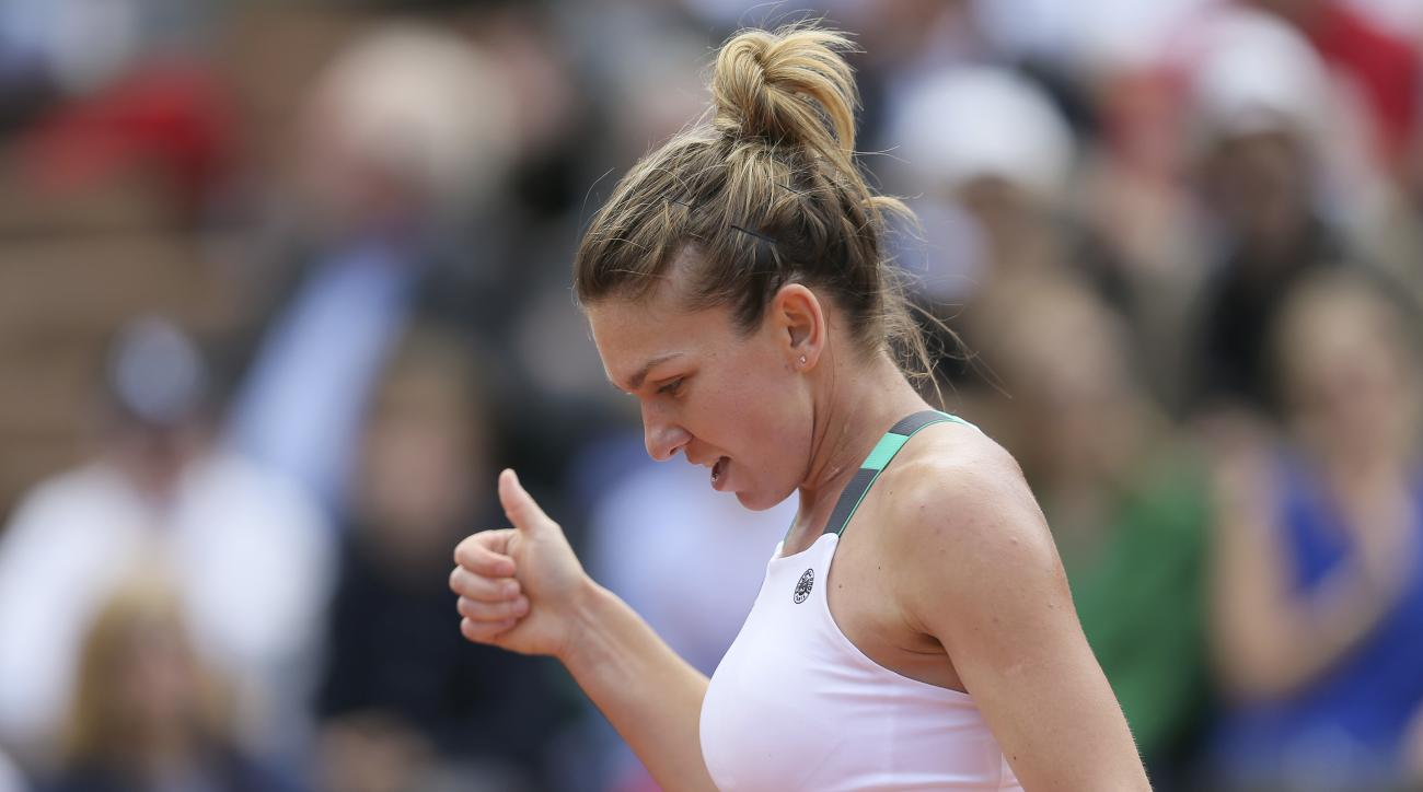 Romania's Simona Halep gives a thumbs up in her quarterfinal match against Ukraine's Elina Svitolina of the French Open tennis tournament at the Roland Garros stadium, in Paris, France. Wednesday, June 7, 2017. (AP Photo/David Vincent)
