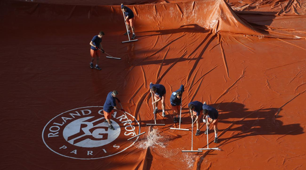 FILE - In this Tuesday, June 6, 2017 file photo workers remove water from the tarpaulin covering the court as rain showers suspended the quarterfinal match of Denmark's Caroline Wozniacki and Latvia's Jelena Ostapenko of the French Open tennis tournament
