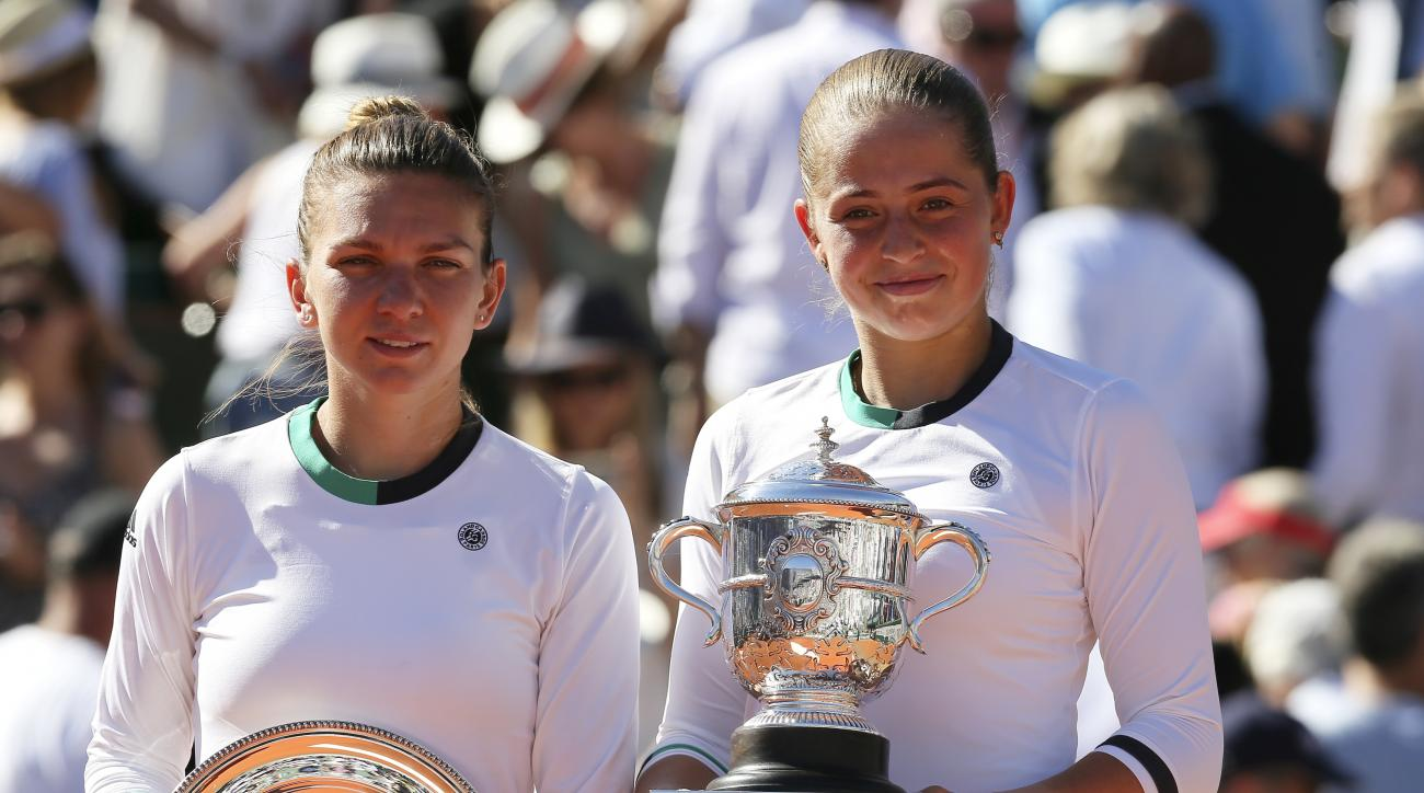 Latvia's Jelena Ostapenko, right, and Romania's Simona Halep hold their trophy after their final match of the French Open tennis tournament at the Roland Garros stadium, Saturday, June 10, 2017 in Paris. Ostapenko won 4-6, 6-4, 6-3. (AP Photo/David Vincen