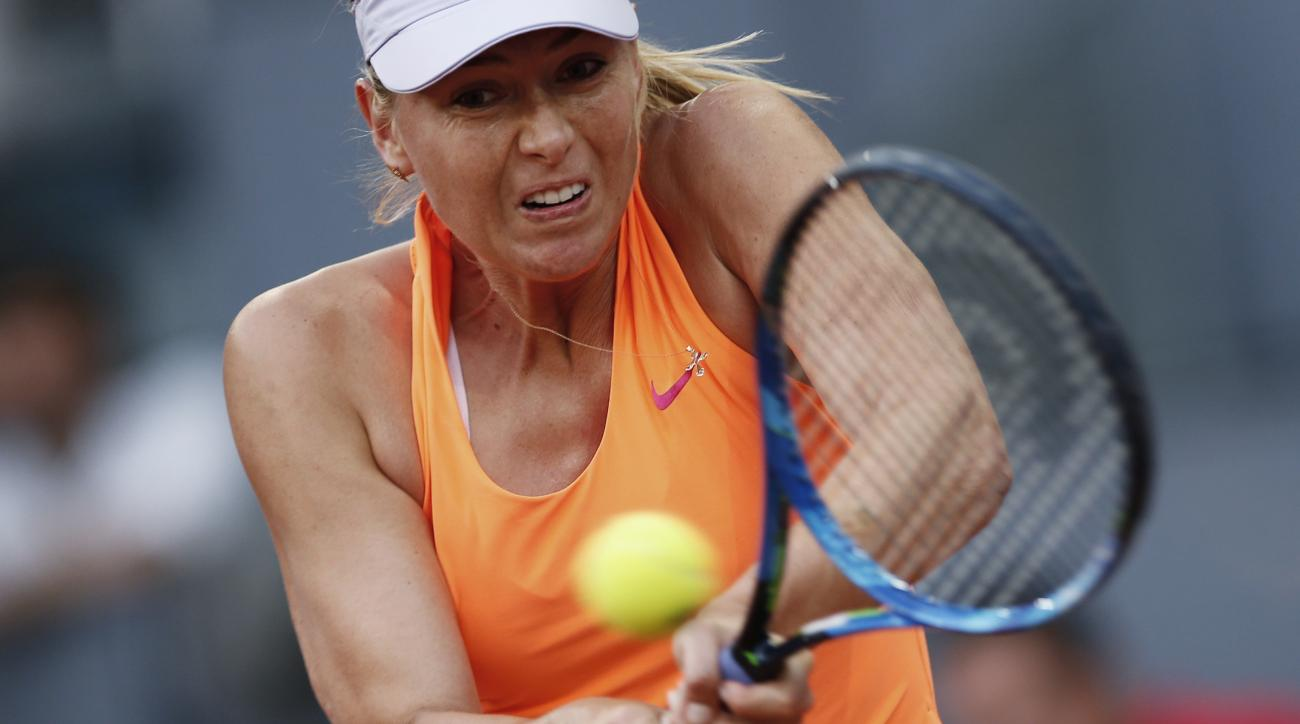 FILE - In this May 8, 2017, file photo, Maria Sharapova hits a return to Eugenie Bouchard, of Canada, during a Madrid Open tennis tournament match in Madrid, Spain. Sharapova has pulled out of Wimbledon qualifying because of an injured left thigh. Sharapo