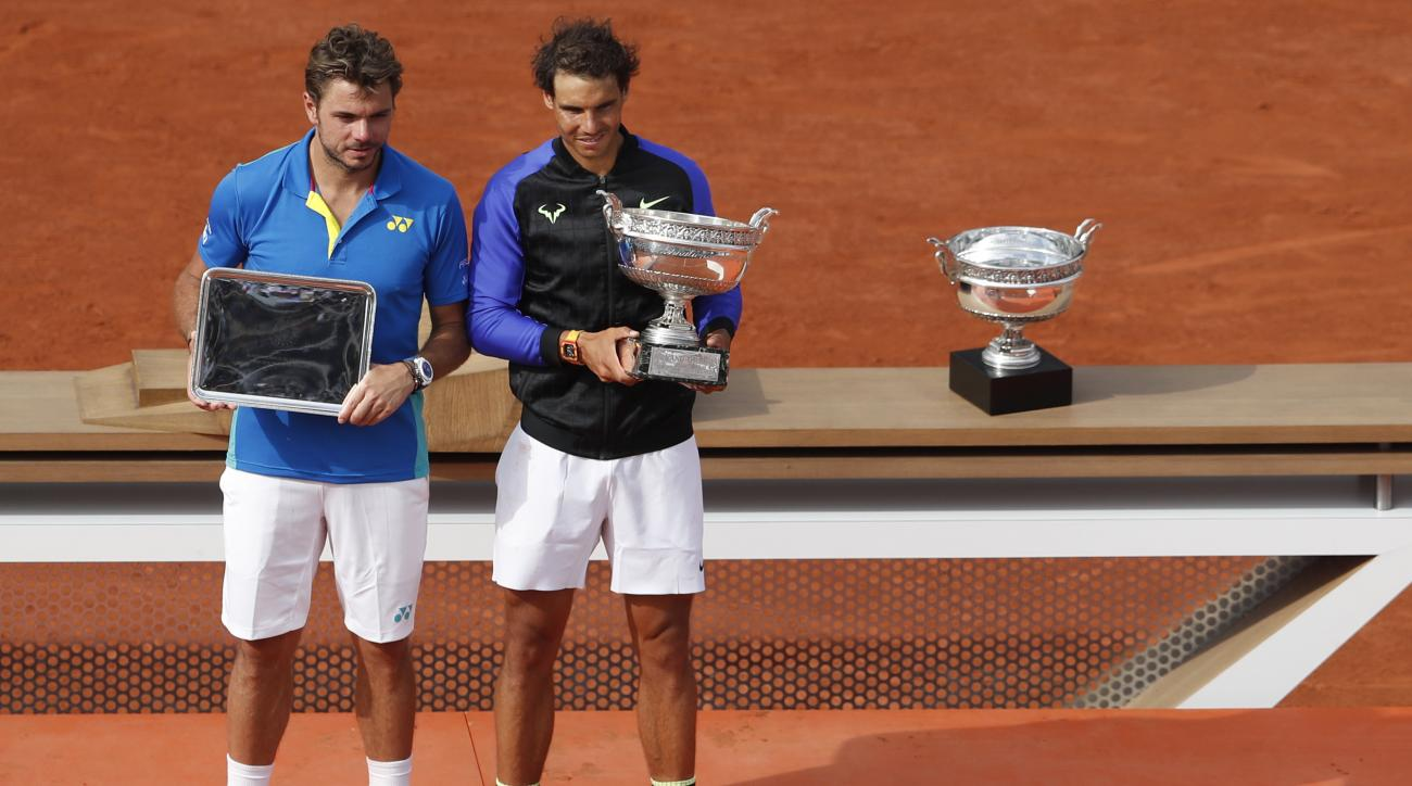 Spain's Rafael Nadal, right, holds the trophy as he celebrates winning his tenth French Open title against Switzerland's Stan Wawrinka, left, in three sets, 6-2, 6-3, 6-1, during their men's final match of the French Open tennis tournament at the Roland G