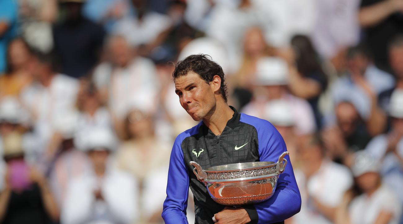 An emotional Rafael Nadal of Spain holds the trophy as he celebrates winning his tenth French Open title against Switzerland's Stan Wawrinka in three sets, 6-2, 6-3, 6-1, during their men's final match of the French Open tennis tournament at the Roland Ga