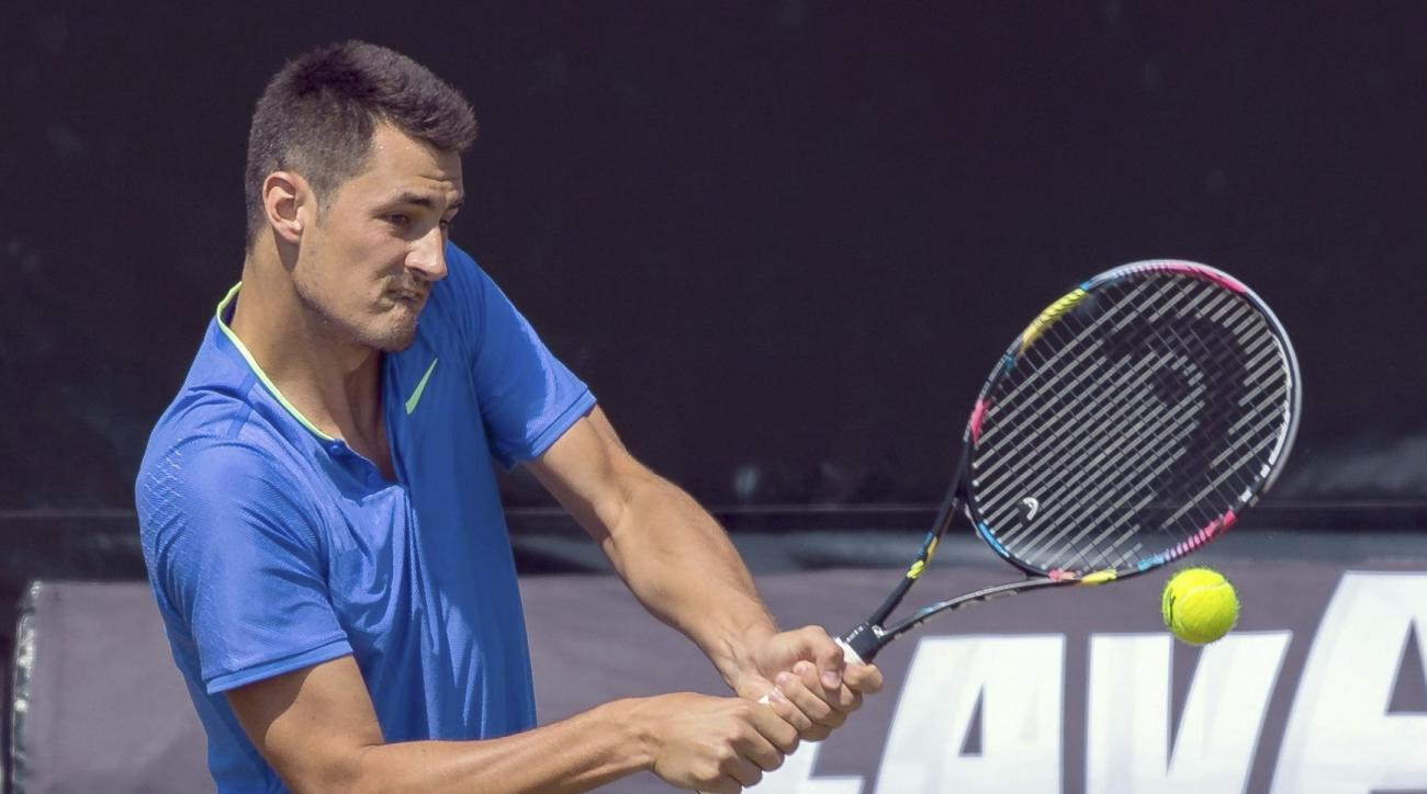 Bernard Tomic of Australia returns the ball to Tomas Berdych of the Czech Republic during their match at the Mercedes Cup tennis tournament  in Stuttgart, Germany, Thursday, June 15, 2017. (Daniel Maurer/dpa via AP)