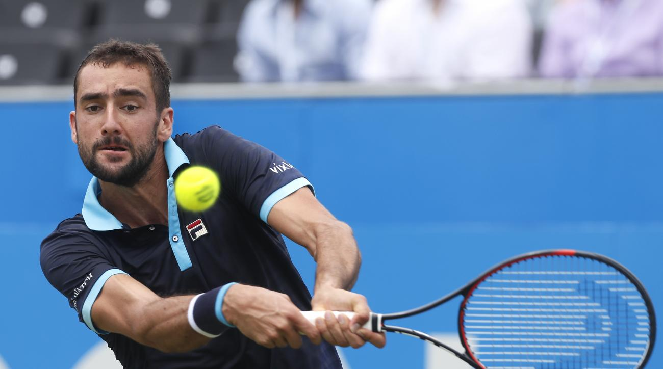 Marin Cilic of Croatia plays a return to Stefan Kozlov of the United States during day four of the Queen's Club tennis tournament in London, Thursday, June 22, 2017. (AP Photo/Kirsty Wigglesworth)