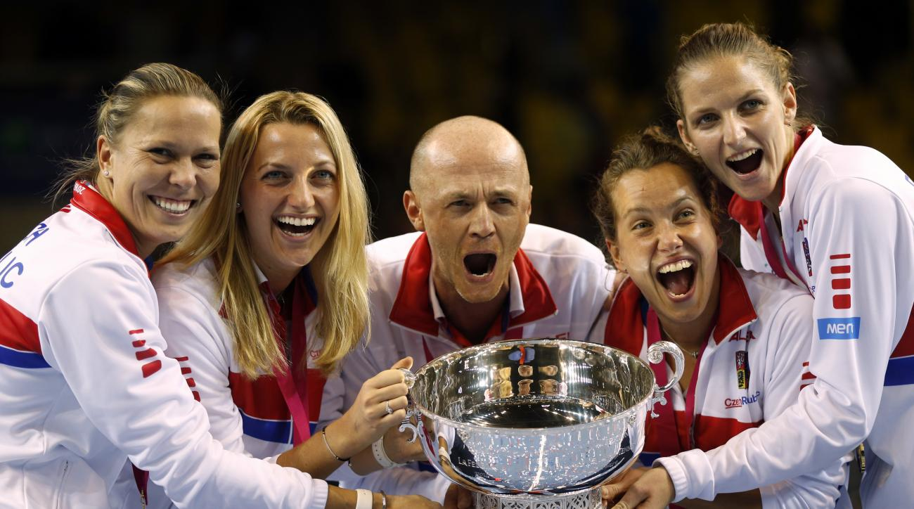 FILE - This is a Sunday, Nov. 13, 2016 file photo of the  Czech Republic team captain Petr Pala, center, and players hold the trophy after their victory against France, during the Fed Cup final in Strasbourg, eastern France.  The Davis Cup and Fed Cup are