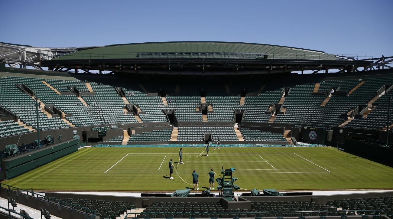 Ground staff water court number one, one day ahead of the start of the Wimbledon Tennis Championships in London Sunday, July 2, 2017. (AP Photo/Alastair Grant)