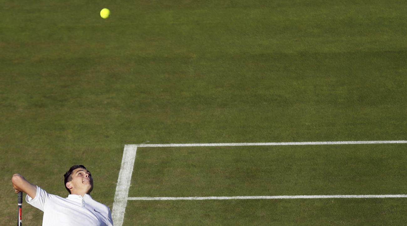 Taylor Fritz of the United States serves to John Isner of the United States during their Men's Singles Match on day two at the Wimbledon Tennis Championships in London Tuesday, July 4, 2017. (AP Photo/Tim Ireland)