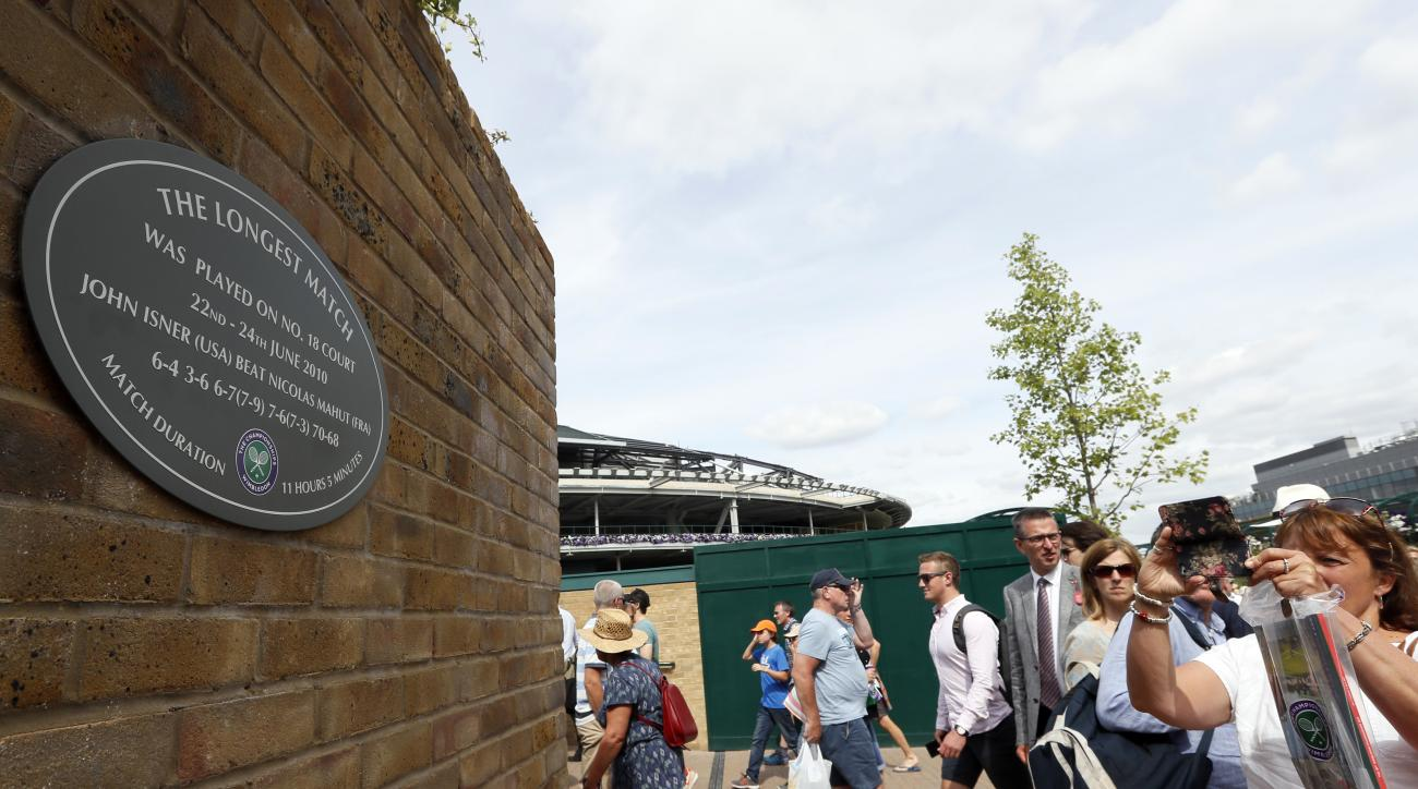 In this photo taken on Tuesday, July 4, 2017, people photograph a plaque at the Wimbledon Tennis Championships in London. And the All England Club insists there is a very simple explanation for why the marker posted on a brick wall outside Court 18 - noti