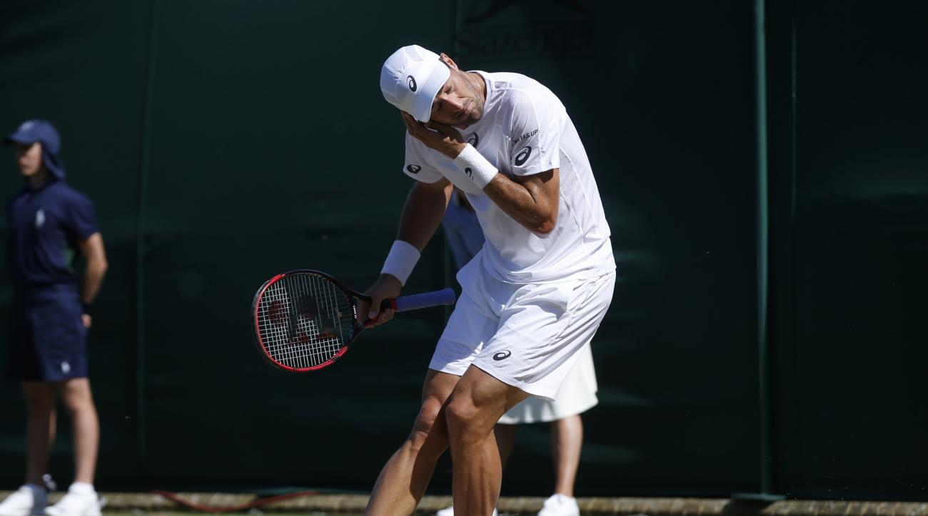 Steve Johnson of the United States gestures to get rid of flying ants during the Men's Singles Match against Moldova's Radu Albot on day three at the Wimbledon Tennis Championships in London Wednesday, July 5, 2017. (AP Photo/Alastair Grant)