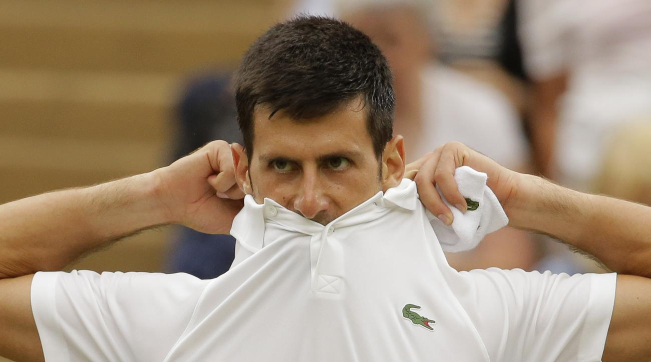 Serbia's Novak Djokovic changes his shirt as he plays his Men's Singles Match against Adrian Mannarino of France on day eight at the Wimbledon Tennis Championships in London Tuesday, July 11, 2017. (AP Photo/Tim Ireland)