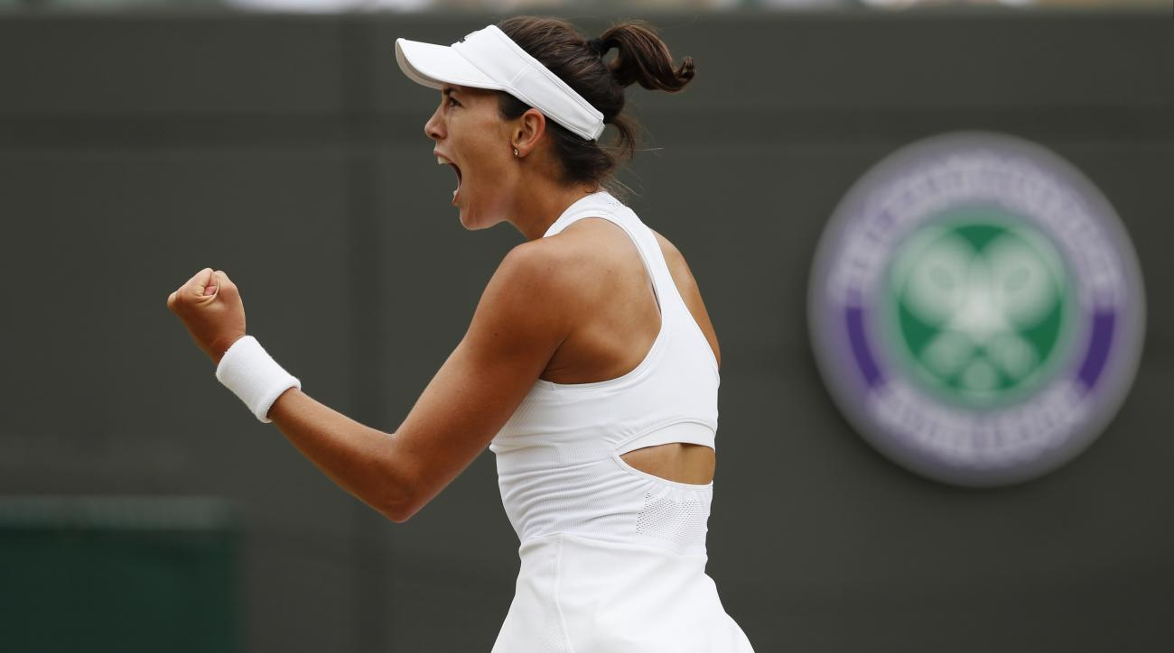 Spain's Garbine Muguruza celebrates winning the first set against Russia's Svetlana Kuznetsova during their Women's Quarterfinal Singles Match on day eight at the Wimbledon Tennis Championships in London Tuesday, July 11, 2017. (AP Photo/Kirsty Wiggleswor