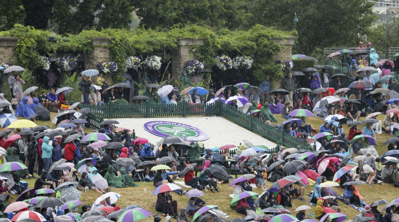 FILE - In this Tuesday, July 11, 2017 file photo spectators sitting on 'Murray Mound' shelter under umbrellas as they watch the Women's Quarterfinal Singles Match between Romania's Simona Halep and Britain's Johanna Konta on the big screen on day eight at
