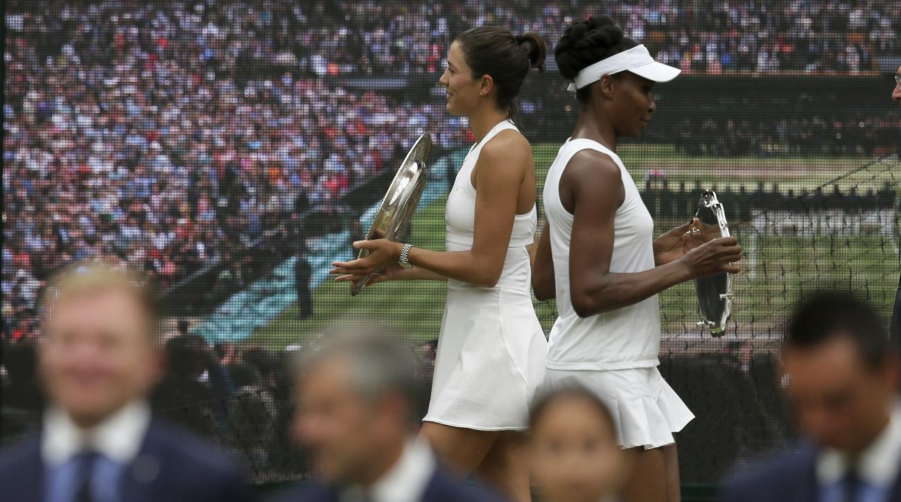 Spain's Garbine Muguruza, left, holds the winners trophy after defeating Venus Williams of the United States, right, in the Women's Singles final match on day twelve at the Wimbledon Tennis Championships in London Saturday, July 15, 2017. (AP Photo/Tim Ir