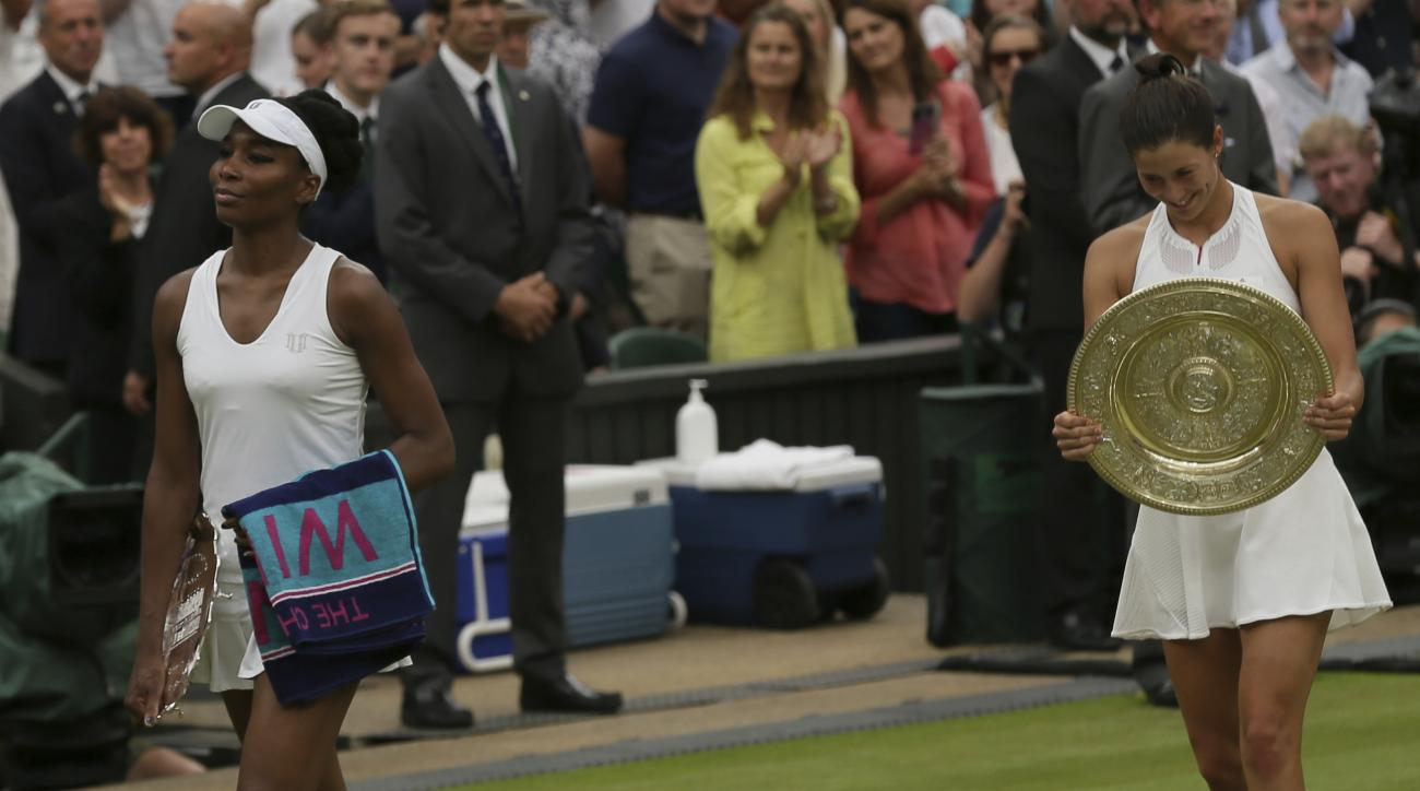Venus Williams of the United States, left leaves with her runner-up trophy from Centre Court after her defeat by Spain's Garbine Muguruza, right, in Women's Singles final on day twelve at the Wimbledon Tennis Championships in London Saturday, July 15, 201