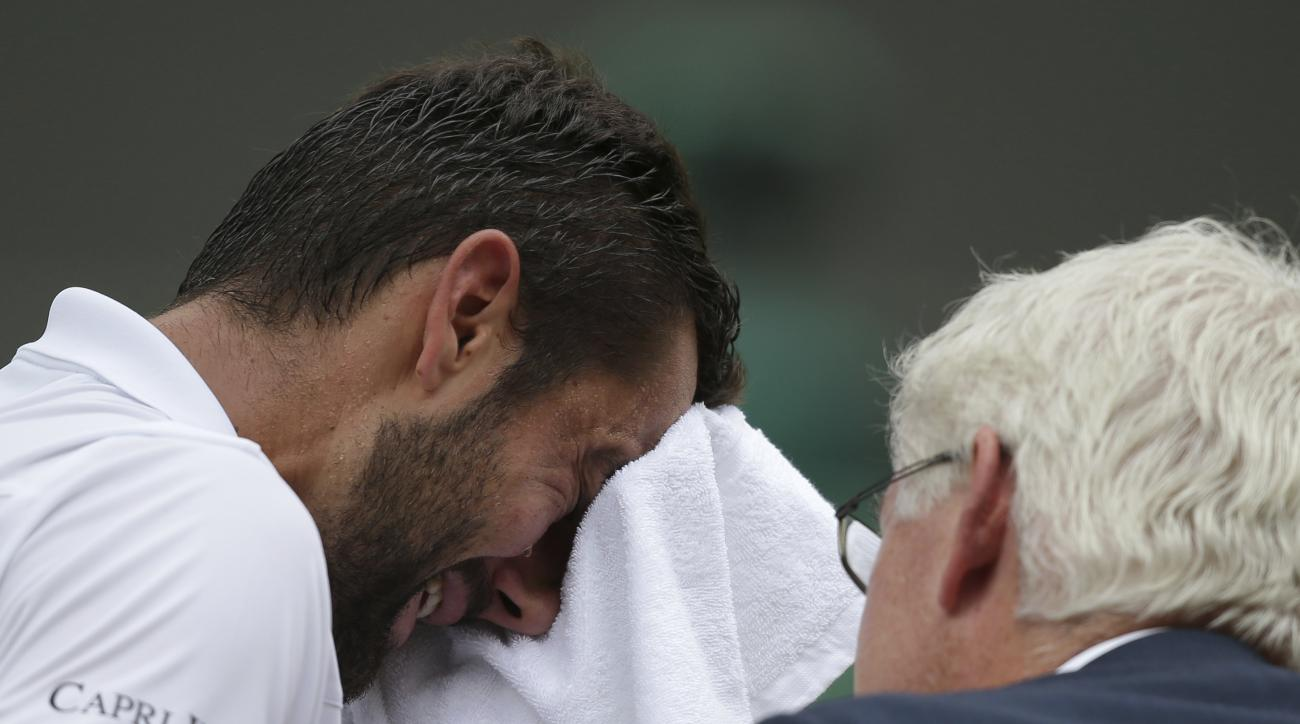 Croatia's Marin Cilic has treatment on his foot as he takes a medical timeout during the Men's Singles final match against Switzerland's Roger Federer on day thirteen at the Wimbledon Tennis Championships in London Sunday, July 16, 2017. (Daniel Leal-Oliv