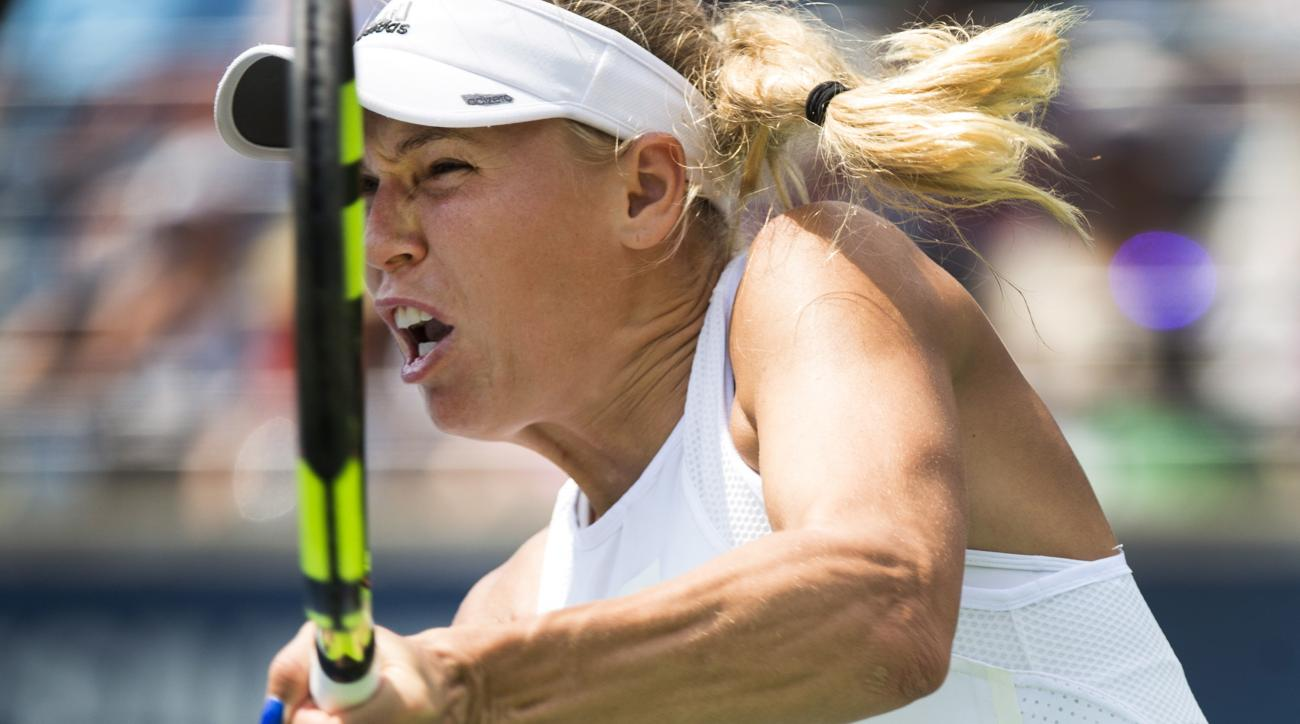 Caroline Wozniacki, of Denmark, returns the ball against Agnieszka Radwanska, of Poland, during a women's third round match at the Rogers Cup tennis tournament in Toronto, Thursday, Aug. 10, 2017. (Nathan Denette/The Canadian Press via AP)
