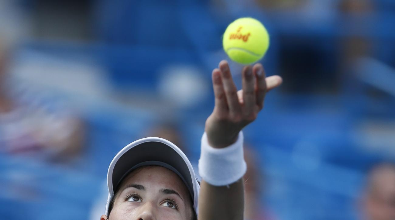 Garbine Muguruza, of Spain, serves to Svetlana Kuznetsova, of Russia, at the Western & Southern Open tennis tournament, Friday, Aug. 18, 2017, in Mason, Ohio. (AP Photo/John Minchillo)