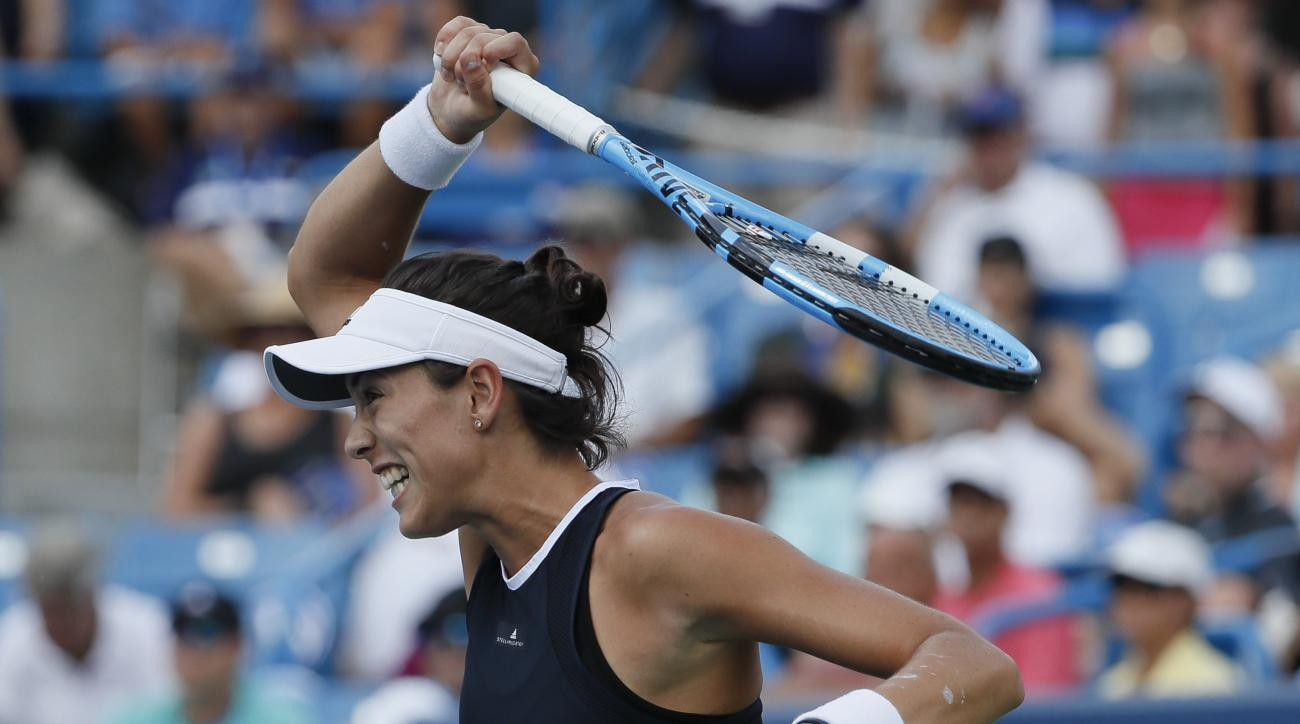 File-This Aug. 20, 2017, file photo shows Garbine Muguruza, of Spain, returning to Simona Halep, of Romania, during the women's singles final at the Western & Southern Open in Mason, Ohio.  (AP Photo/John Minchillo, File)