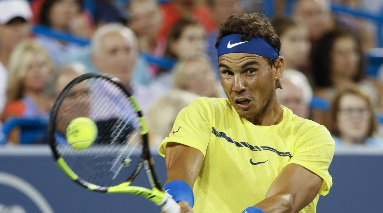 File-This Aug. 18, 2017, file photo shows Rafael Nadal, of Spain, returning to Nick Kyrgios, of Australia, at the Western & Southern Open tennis tournament in Mason, Ohio. (AP Photo/John Minchillo, File)
