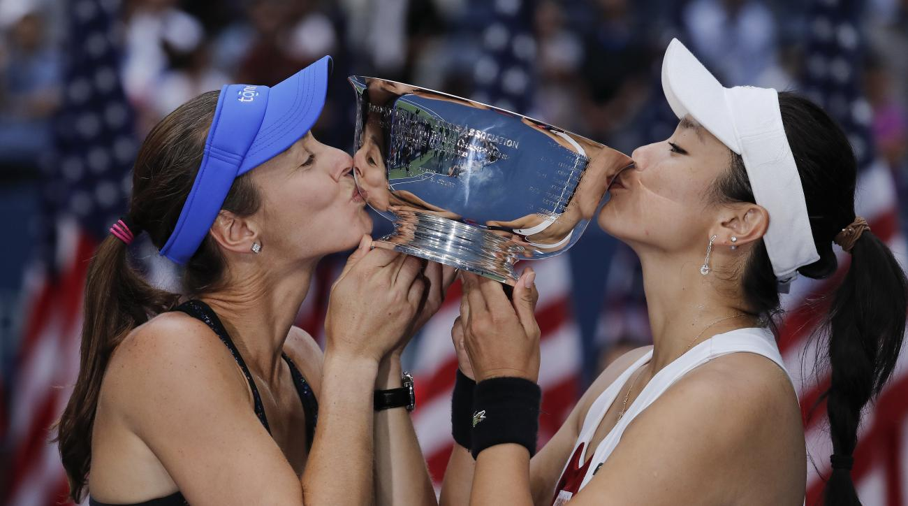 Martina Hingis, of Switzerland, left, and Chan Yung-Jan, of Taiwan, hold up the women's doubles championship trophy after beating Katerina Siniakova, of Czech Republic, and Lucie Hradecka, of the Czech Republic, in the women's doubles final of the U.S. Op