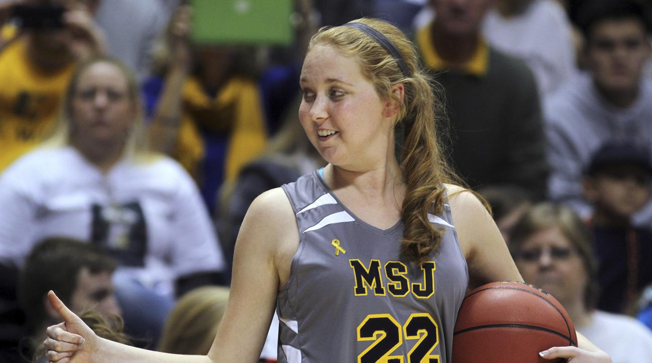 FILE - In this Nov. 2, 2014, file photo, Mount St. Joseph's Lauren Hill gives a thumbs-up as she holds the game ball during her first NCAA college basketball game against Hiram University at Xavier University in Cincinnati. Schools that helped a college b