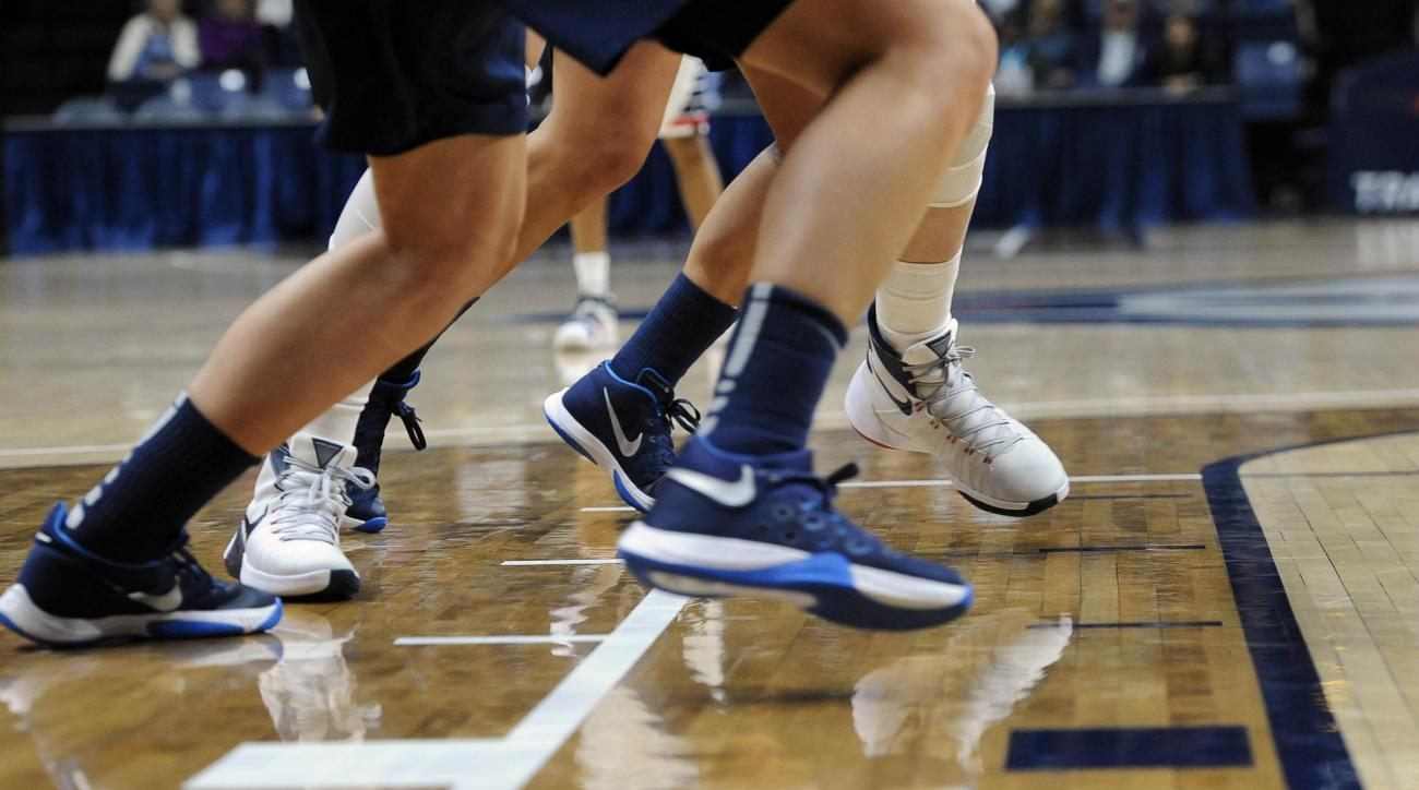Connecticut and Vanguard players advance over a new lane indicated by a white line during an NCAA college exhibition basketball game Sunday, Nov. 8, 2015, in Storrs, Conn. UConn used some experimental rules, including a men's basketball, a 24-second shot