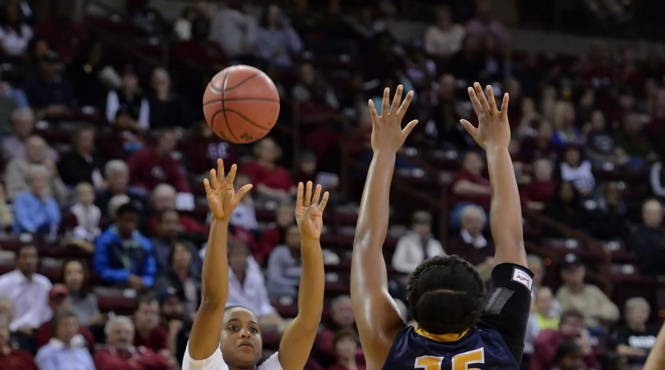 South Carolina's Shay Colley shoots a 3-pointer while defended by UNC Greensboro's Jade Scaife during the first half of an NCAA college basketball game Sunday, Nov. 15, 2015, in Columbia, S.C. (AP Photo/Richard Shiro)