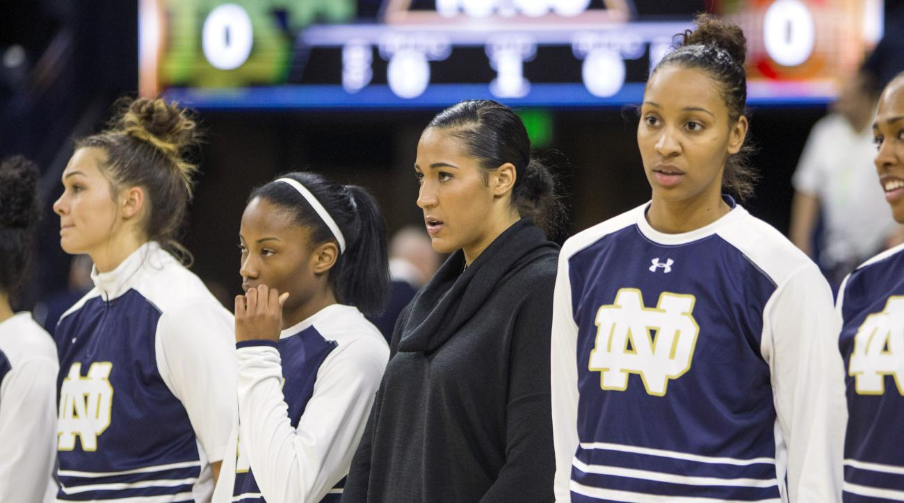Notre Dame's Taya Reimer, center, stands with teammates during the National Anthem before sitting out an NCAA college basketball game on Wednesday, Dec. 2, 2015, in South Bend, Ind. (AP Photo/Robert Franklin)