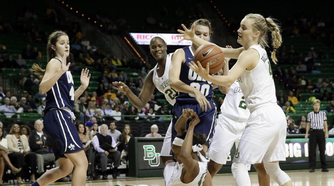 Baylor guard Kristy Wallace, right, takes control of a rebound as Nina Davis falls to the court while competing for the ball against Oral Roberts' Maria Martianez (44) and Blair Bryce (30) during the second half of an NCAA college basketball game Thursday
