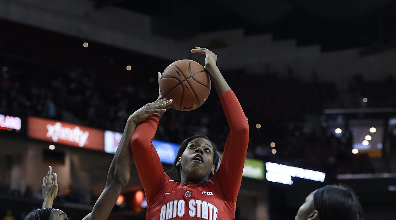 Ohio State's Lisa Blair shoots between Shatori Walker-Kimbrough, left, and A'Lexus Harrison during the second half of an NCAA college basketball game, Saturday, Jan. 2, 2016, in College Park, Md. Ohio State won 80-71. (AP Photo/Gail Burton)
