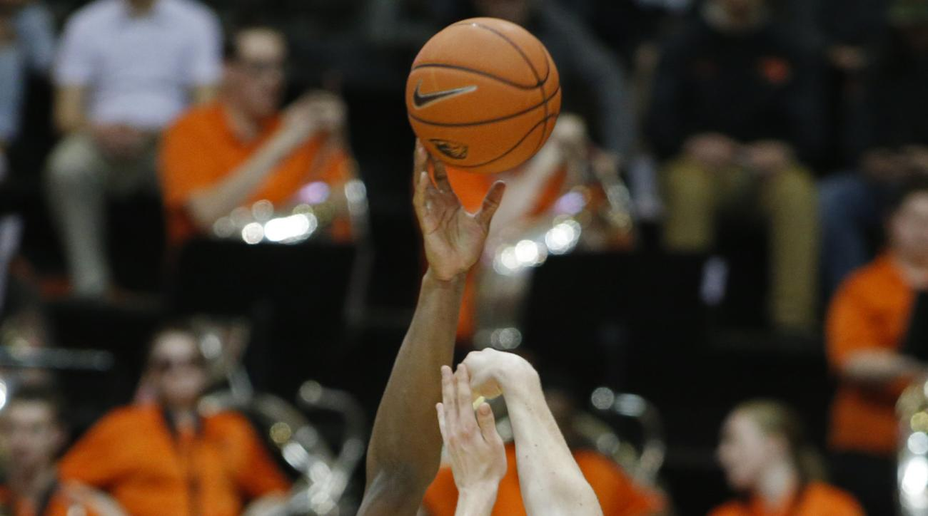 Colorado's Tory Miller, left, blocks the shot of Oregon State's Olaf Schaftenaar in the first half of an NCAA college basketball game in Corvallis, Ore., on Saturday, Feb. 6, 2016. (AP Photo/Timothy J. Gonzalez)