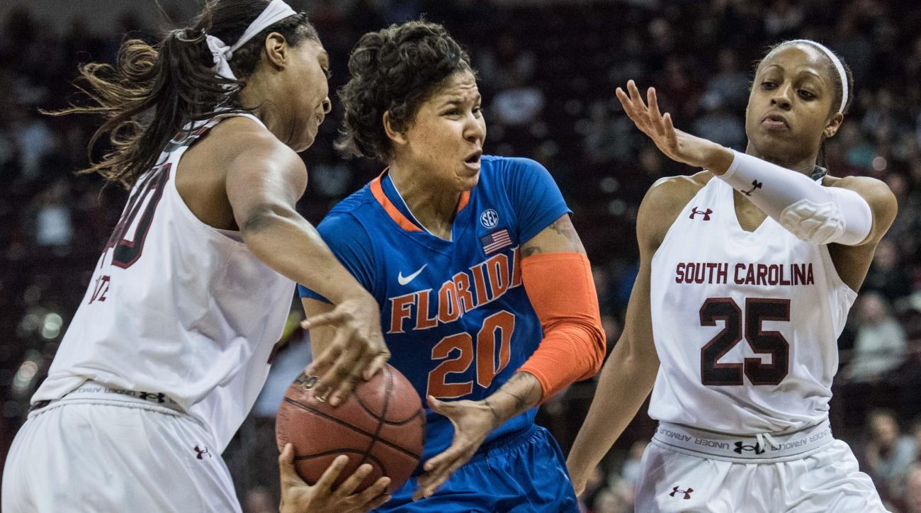 Florida guard Simone Westbrook (20) drives to the hoop defended by South Carolina forward Jatarie White, left, and South Carolina guard Tiffany Mitchell (25) during the first half of an NCAA college basketball game Thursday, Feb. 11, 2016, in Columbia, S.