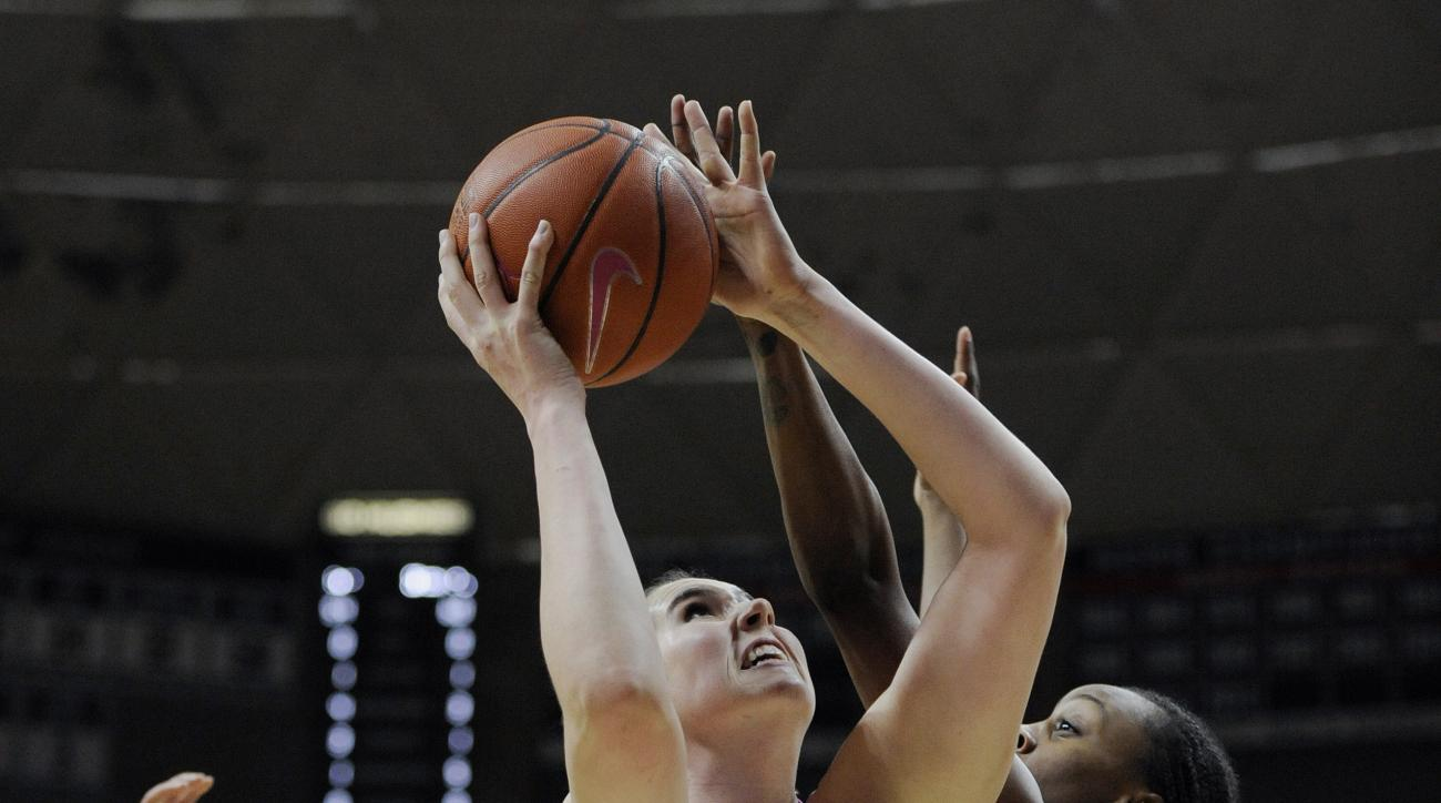 Connecticut's Natalie Butler, center, shoots over Cincinnati's Brandey Tarver, right, during the first half of an NCAA college basketball game Wednesday, Feb. 17, 2016, in Storrs, Conn. (AP Photo/Jessica Hill)