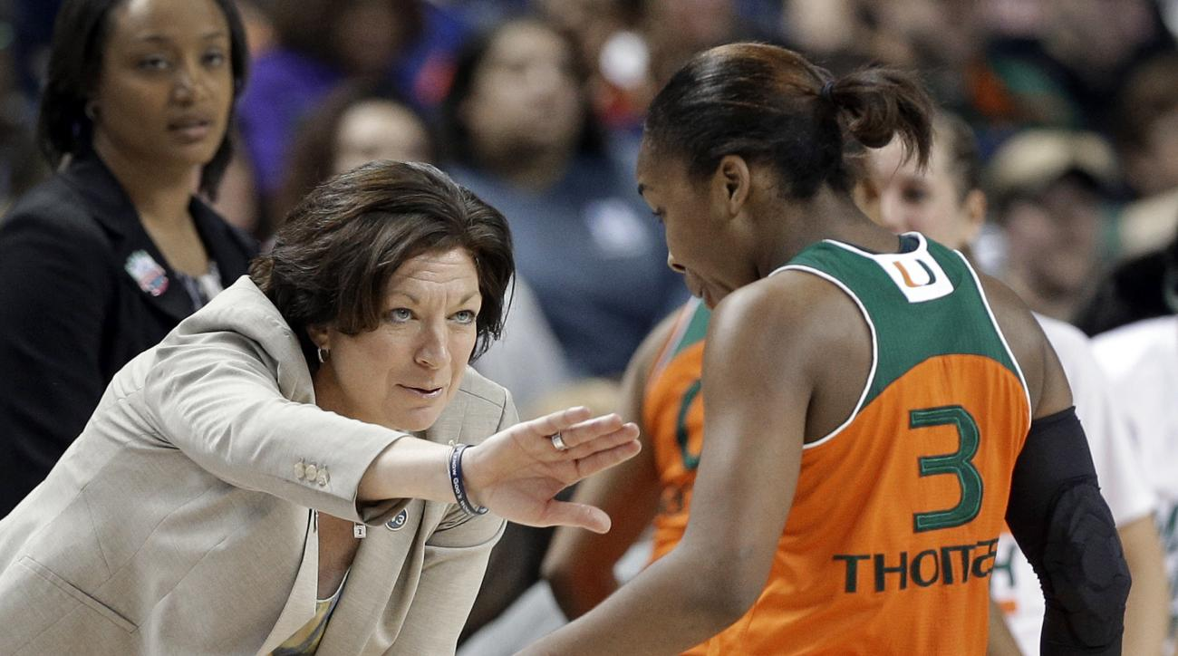 Miami head coach Katie Meier, left, reaches out to Jessica Thomas, right, during the second half of an NCAA college basketball game against Notre Dame in the Atlantic Coast Conference tournament in Greensboro, N.C., Saturday, March 5, 2016. Notre Dame won