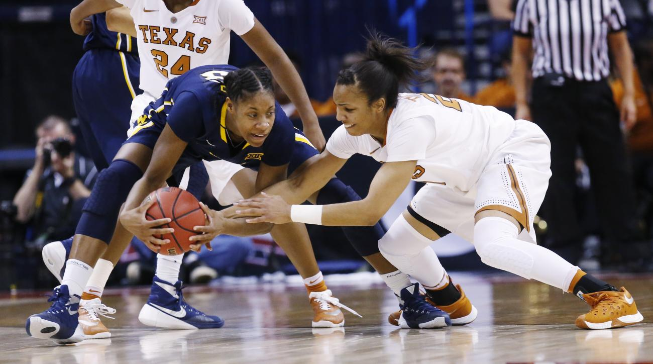 Texas guard Brianna Taylor, right, reaches in for a ball held by West Virginia guard Bria Holmes, left, in the second quarter of an NCAA college basketball game in the Big 12 women's tournament in Oklahoma City, Sunday, March 6, 2016. (AP Photo/Sue Ogrock