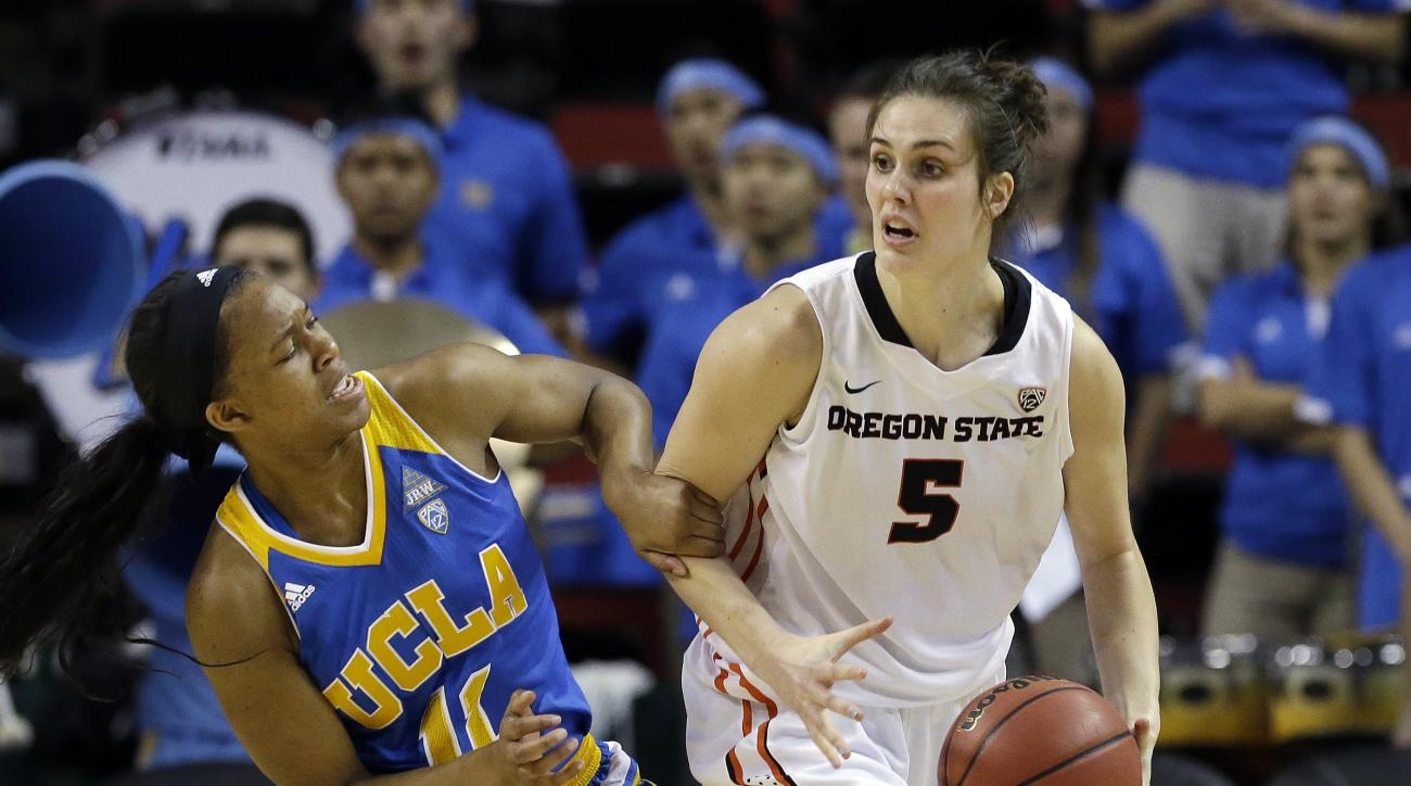 UCLA's Lajahna Drummer (11) grabs Oregon State's Samantha Siegner in the first half of an NCAA college basketball game in the championship game of the Pac-12 Conference tournament, Sunday, March 6, 2016, in Seattle. (AP Photo/Elaine Thompson)