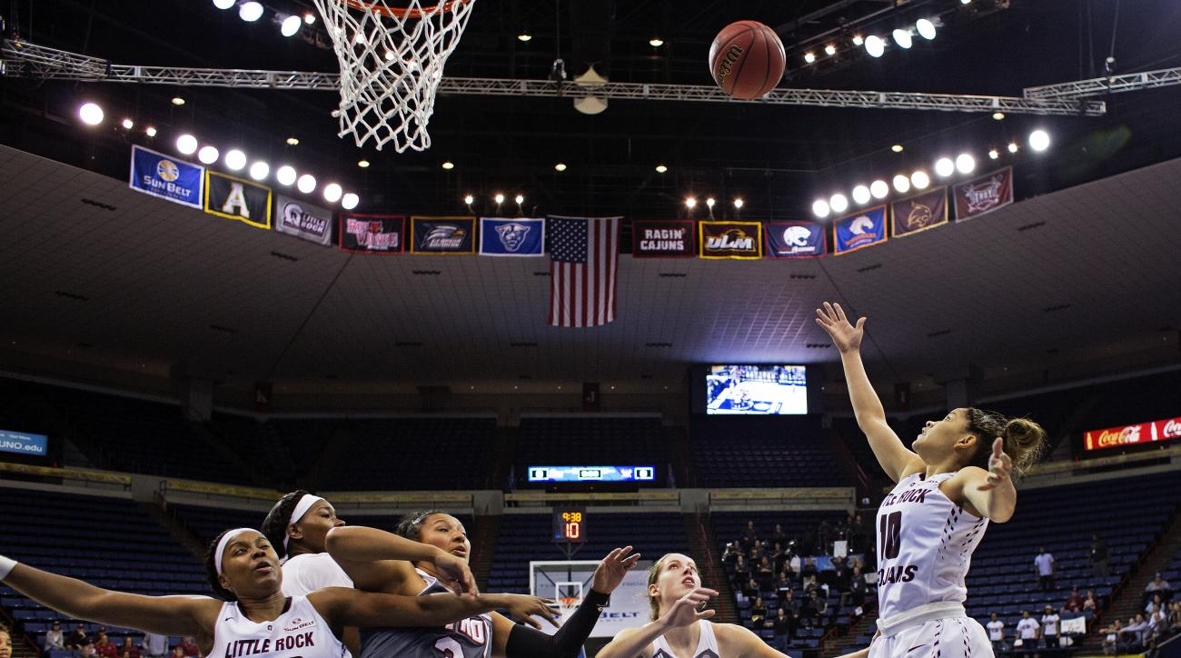 Arkansas Little Rock guard Alexius Dawn (10) makes a shot over Troy forward Kristen Emerson (23) and forward Caitlyn Ramirez (34) in the first half of an NCAA college basketball game in the championship of the Sun Belt Conference women's tournament in New