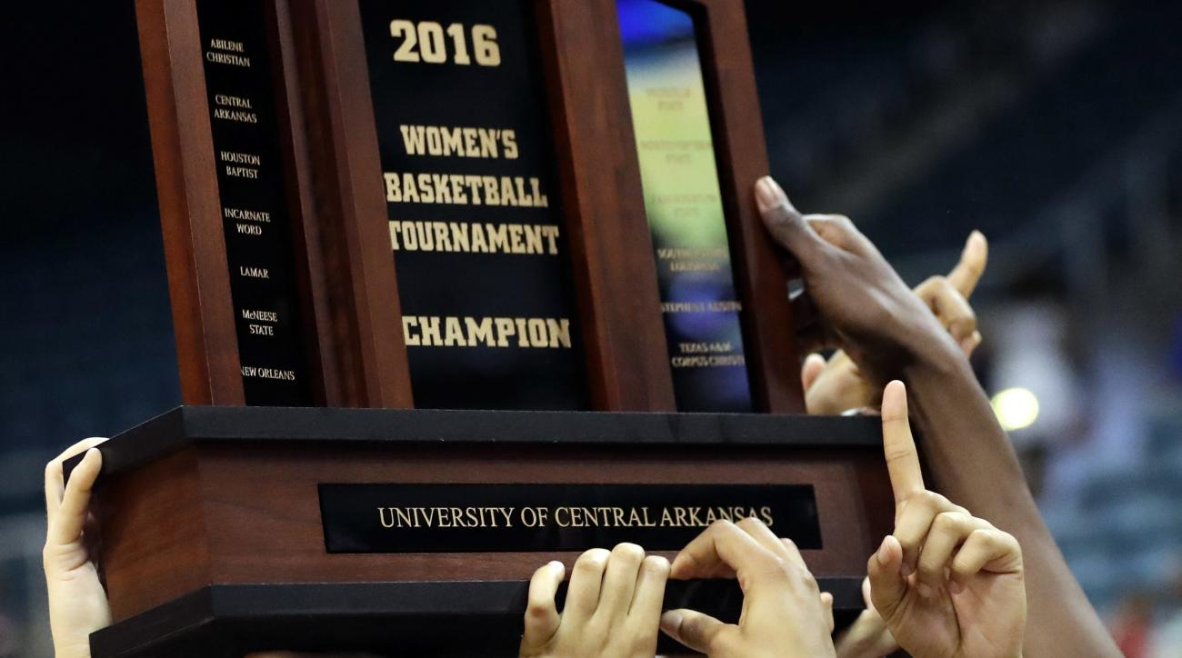 Central Arkansas players hold up the winner's trophy after defeating Sam Houston State in an NCAA college basketball game in the championship of the Southland Conference tournament, Sunday, March 13, 2016, in Katy, Texas. (AP Photo/David J. Phillip)