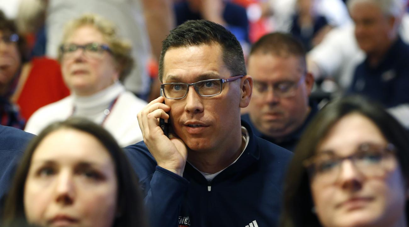 Duquesne head coach Dan Burt is on the phone as he waits with his team to hear for their first-ever berth in the NCAA women's college basketball tournament on Monday, March 14, 2016, in Pittsburgh. Duquesne will play Seton Hall in their first-ever NCAA to